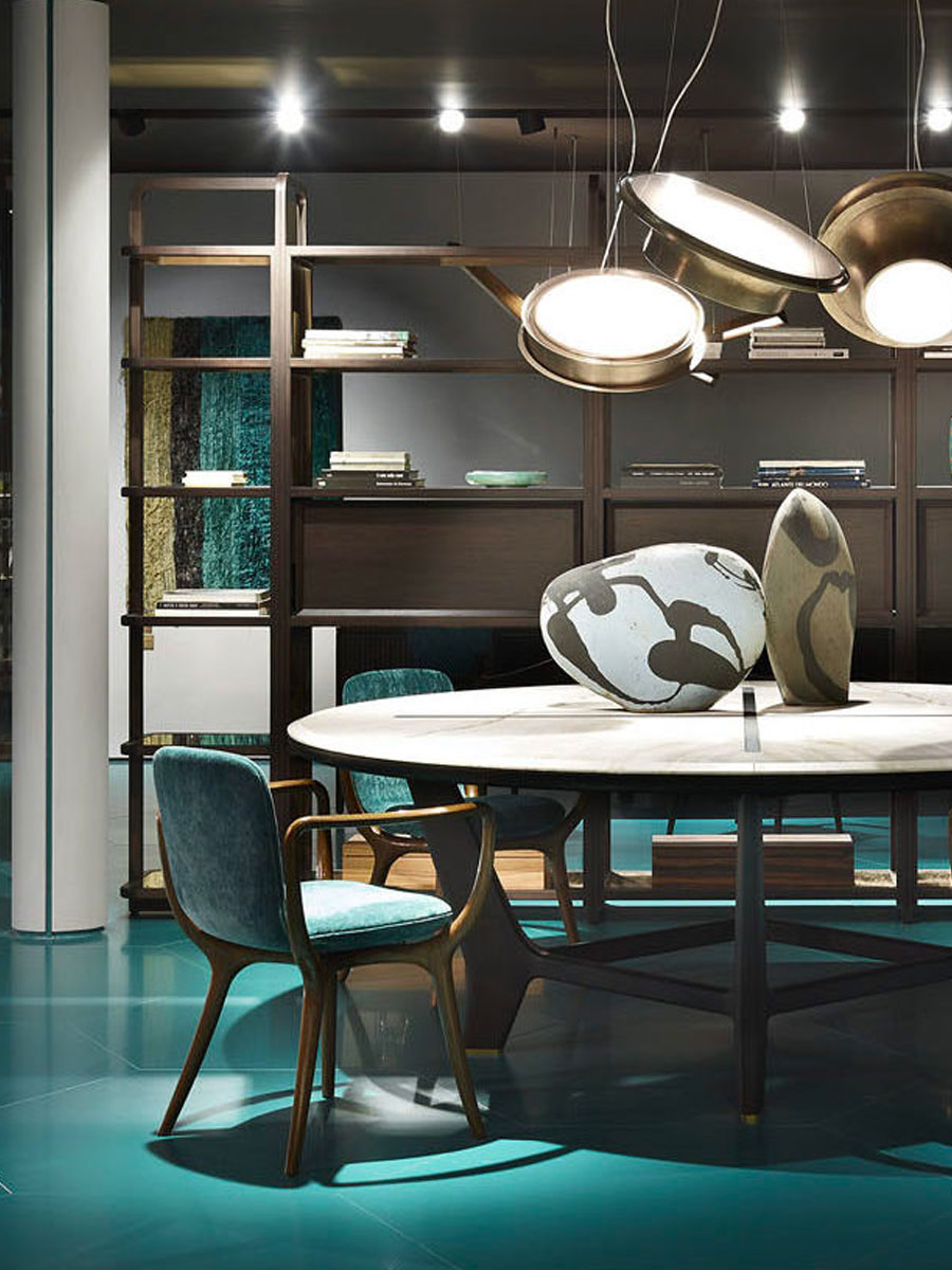 Ceccotti showroom in Chelsea Harbour with teal floor, round dining table and upholstered teal dining chairs
