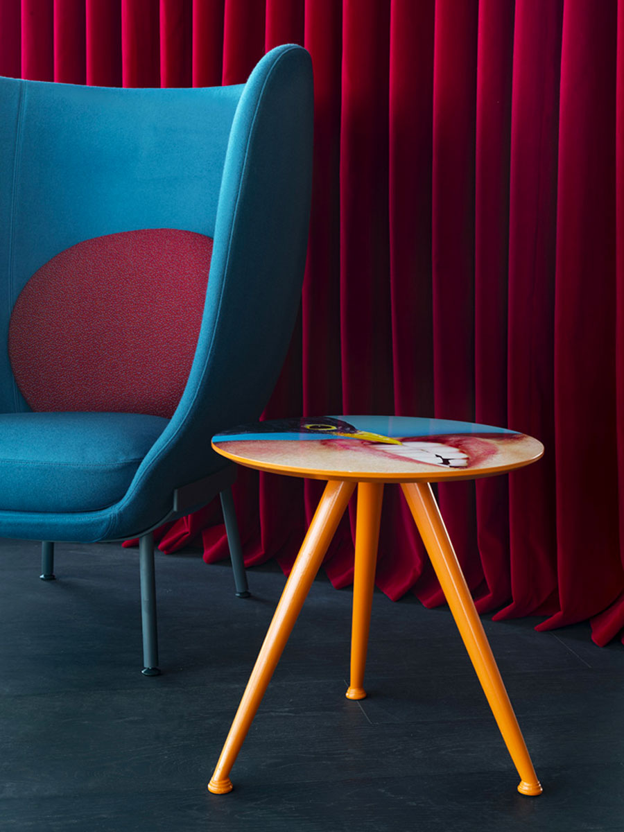 Blue armchair with deep red curtain wall and printed round side table
