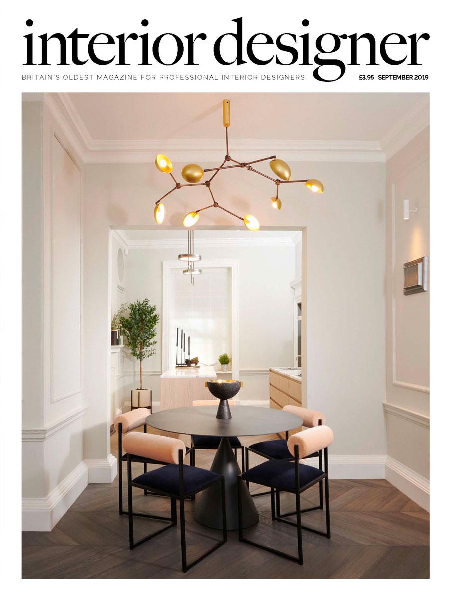 Dining room with white walls, round dark table and upholstered dining chairs with peach detail and gold chandelier