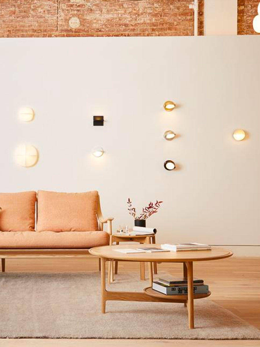 Bright space with white walls and wall lamps and peach sofa