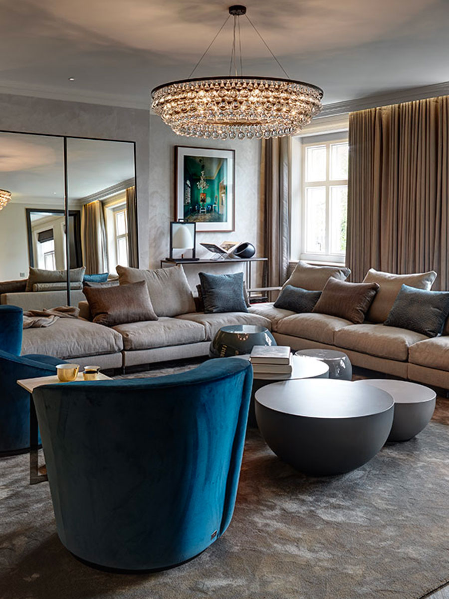 Living Room featuring a long L shape sofa and crystal chandelier designed by Tollgard Design Group