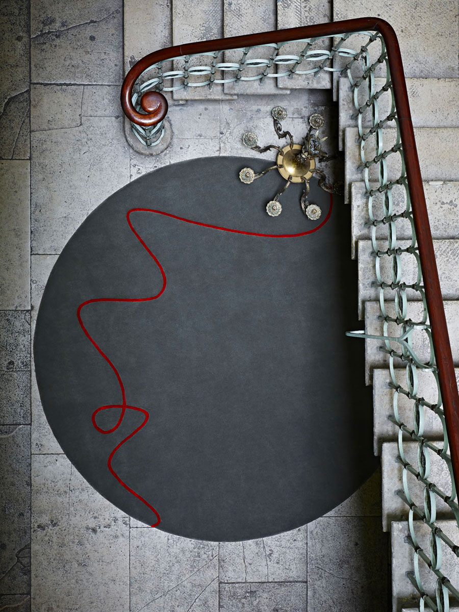 round rug designed by Staffan Tollgard in grey with red thread at the base of a staircase