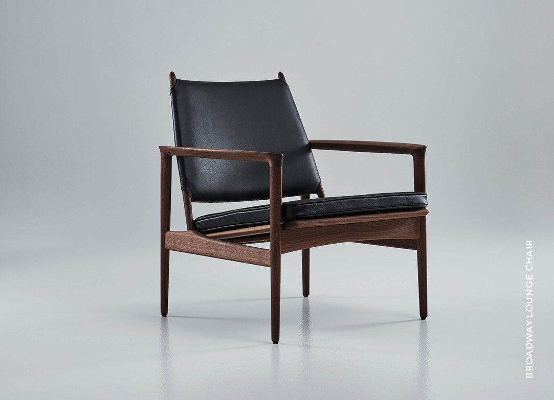 Eikund Broadway lounge chair ioled walnut and black leather upholstery in white background