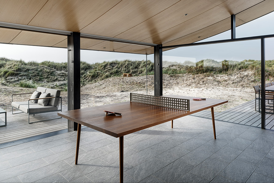 Ping pong table at modern danish summer house with dunes background