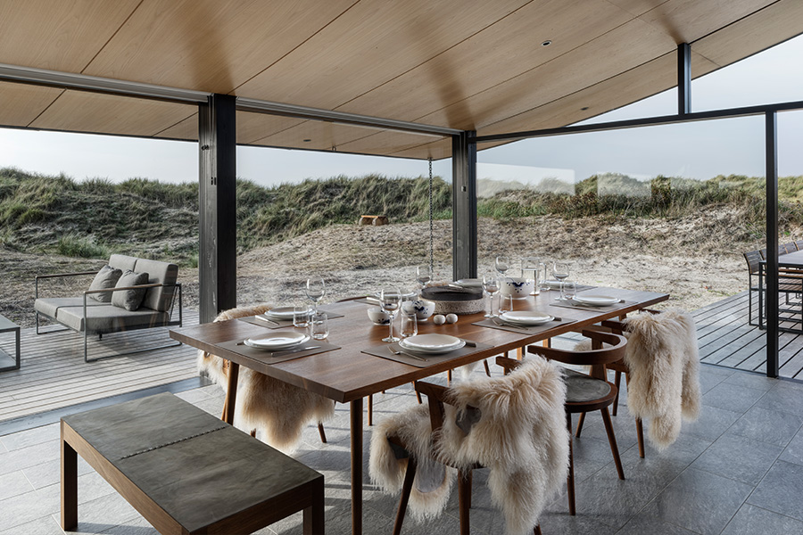 Wooden dining table at modern danish summer house with dunes background