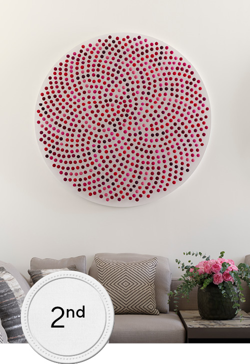 Living room ambient shot wih beige l shape sofa and round pink artipiece above